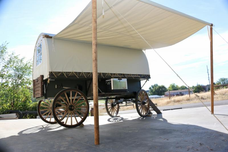 this sheep wagon built on amish woodspoke running gear , with awing